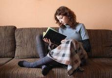 Mujer rizada con el libro que se sienta en el sofá Fotos de archivo