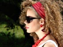 Mujer rizada con joyería roja Fotos de archivo