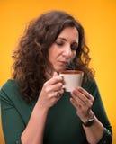 Mujer rizada con una taza de té o de café Imagenes de archivo