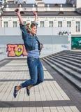 Mujer rizada del inconformista joven que escucha la música en la ciudad Foto de archivo
