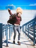 Mujer rizada del inconformista joven que se divierte en el centro de la ciudad de la ciudad Foto de archivo