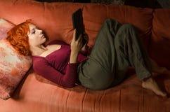 Mujer rizada en un sofá con el ebook Foto de archivo libre de regalías