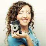 Mujer rizada joven con la cámara del vintage Fotos de archivo