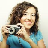 Mujer rizada joven con la cámara del vintage Fotografía de archivo