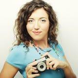 Mujer rizada joven con la cámara del vintage Fotografía de archivo libre de regalías