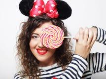 Mujer rizada joven con los oídos de ratón que sostienen la piruleta Fotos de archivo