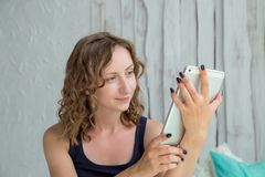 Mujer rizada joven que miente en la cama con PC de la tableta Fotografía de archivo libre de regalías