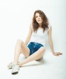 Mujer rizada joven que se sienta en el piso, ropa de sport Foto de archivo libre de regalías