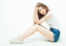 Mujer rizada joven que se sienta en el piso, ropa de sport Imágenes de archivo libres de regalías