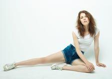 Mujer rizada joven que se sienta en el piso, ropa de sport Imagen de archivo libre de regalías