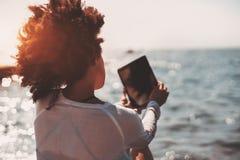 Mujer rizada negra que toma la imagen del horizonte de mar Fotografía de archivo