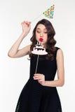 Mujer rizada que sopla en la torta de cumpleaños falsa con los apoyos de las velas foto de archivo libre de regalías