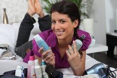 Mujer rodeada por los cosméticos imagen de archivo
