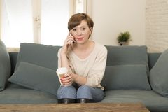 Mujer roja atractiva y feliz joven del pelo que sienta en casa el café de consumición del sofá del sofá que habla en el teléfono  Imagen de archivo libre de regalías