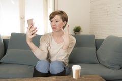 mujer roja atractiva y feliz joven del pelo que sienta en casa el café de consumición del sofá del sofá que toma la imagen del se Fotos de archivo libres de regalías