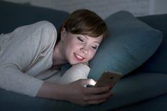 Mujer roja bonita y feliz joven del pelo en su 20s o 30s que miente en el sofá casero o cama usando el teléfono móvil tarde en el fotos de archivo
