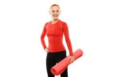 Mujer roja con la estera de la yoga Foto de archivo