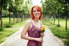 Mujer roja de Heair que sostiene las flores de la primavera Fotografía de archivo libre de regalías