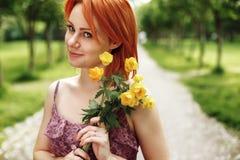Mujer roja de Heair que sostiene las flores de la primavera Imágenes de archivo libres de regalías
