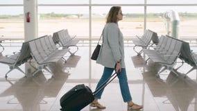 Mujer roja de la muchacha del jengibre del pelo que comprueba al tablero de la salida en el aeropuerto, de la parte posterior almacen de video