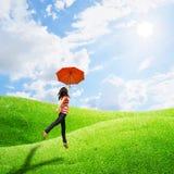 Mujer roja del paraguas en cielo del prado y del sol Imagen de archivo libre de regalías