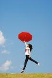 Mujer roja del paraguas que salta al cielo Imagen de archivo libre de regalías