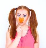 Mujer roja del pelo con caramelo grande del corazón Imagen de archivo libre de regalías