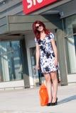 Mujer roja del pelo con el panier contra de la entrada de la tienda Fotografía de archivo