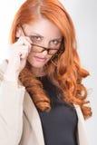 Mujer roja del pelo de Glamorour en vidrios Foto de archivo