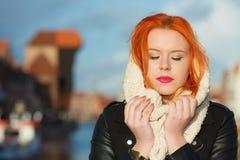 Mujer roja del pelo de la belleza en la ropa caliente al aire libre Fotografía de archivo