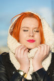 Mujer roja del pelo de la cara de la belleza en la ropa caliente al aire libre Imagenes de archivo