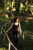 Mujer roja del pelo en bosque verde Fotos de archivo