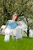 Mujer roja del pelo que goza del sol del resorte en el banco blanco Foto de archivo