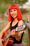 Mujer roja del pelo que toca la guitarra Imagenes de archivo