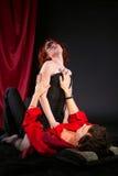 Mujer roja en la máscara en hombre - escena de amor Foto de archivo libre de regalías