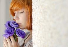 Mujer roja hermosa del pelo que sostiene la flor púrpura Imagenes de archivo