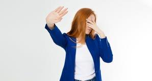 Mujer roja joven del pelo que hace una actitud y un facepalm del rechazo en un fondo blanco Sensaci?n humana negativa de la expre imagenes de archivo