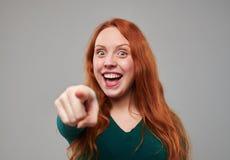 Mujer roja joven emocionada del pelo que señala en usted con índice Imagenes de archivo