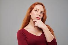 Mujer roja joven pensativa del pelo que lleva a cabo la mano en la barbilla Fotos de archivo