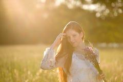 Mujer roja larga del pelo en prado romántico de la puesta del sol imágenes de archivo libres de regalías