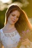 Mujer roja larga del pelo en prado romántico de la puesta del sol imagen de archivo