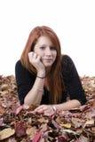Mujer rojiza joven que miente en hojas de otoño Imágenes de archivo libres de regalías