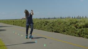 Mujer rollerblading al revés a través de los conos al aire libre almacen de video