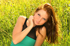 Mujer romántica con el pelo marrón largo en hierba verde del campo Foto de archivo