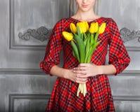 Mujer romántica con el pelo rubio con el ramo del tulipán Foto de archivo