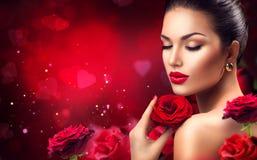 Mujer romántica de la belleza con las flores de la rosa del rojo Foto de archivo libre de regalías