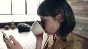 Mujer romántica de la belleza joven que bebe té o el café caliente en luz de la mañana Muchacha relajada feliz que goza de la taz metrajes