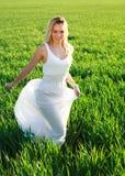 Mujer romántica en el vestido que corre a través de campo verde Fotografía de archivo libre de regalías