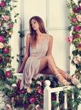 Mujer romántica hermosa con el pelo largo que se sienta y que presenta en el th Foto de archivo libre de regalías