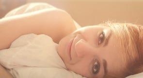 Mujer romántica hermosa en cama de la mañana Fotos de archivo